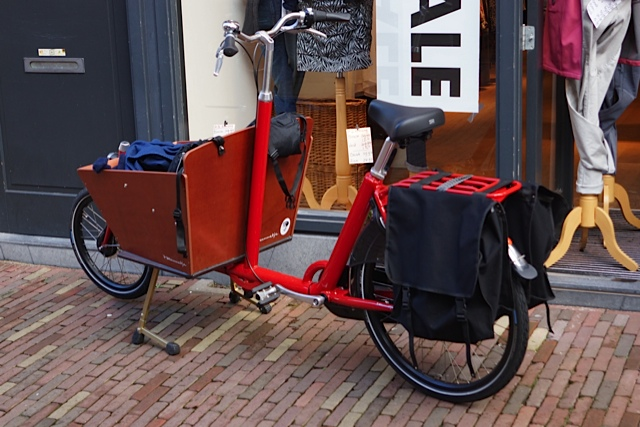 This cargo bike was later seen carrying two small children snugly tucked under a blanket in the cargo box with Mum pedalling.