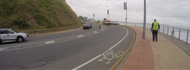 One lane around Kirra Point closes. Yellow safety shirts everywhere.