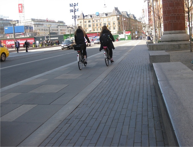A typical scene where cars, bicycles and pedestrians each have their own lane.  To the left is the car lane, then the bicycles, then the footpath is on the right hand side. Each direction of traffic has this set-up