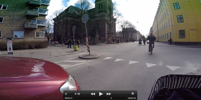 This photo is take from my bicycle handlebars and shows a car holding back to give my bicycle priority in going through this intersection. It's a bit unnerving at first because I'm more accustomed to the car going first.