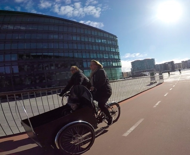 Cargo bike with child in carriage. No cover over the carriage as it was such a beautiful day.