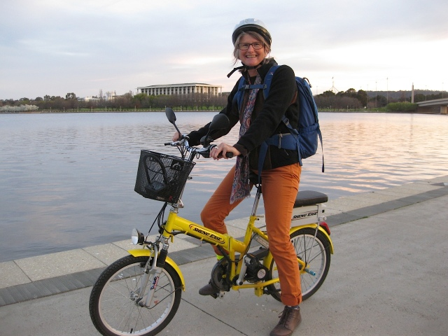 The cute little yellow electric bike by Lake Burley Griffin with The National Library in the background.