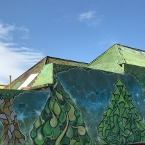 Green street art and old tin roof